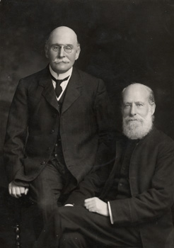 A portrait photograph of Robert and Edward Rudolf. Robert is standing and Edward is seated. Robert was 76 years old, and Edward was 80.