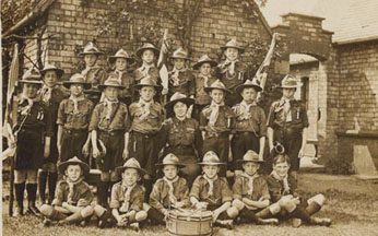 With the exception of their broad-rimmed hats, scouting uniform is very similar today. Each troop would have its own markings which appeared on the children's shirts and on their flags. Matron sits proudly in the middle as Akela.