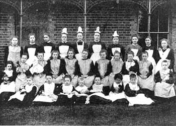 Smocks and pinafores were the ideal clothing for girls' homes, because they could be used for housework and were easily cleaned. They were also smart enough to wear for informal group portraits, as this photograph shows.