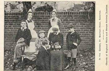Sitting on Matron's knee, the Home's cat forms the centre of attention in this group photograph. The Society believed that keeping a pet encouraged children to be responsible, and taught them 'the many lessons which the care of some gentle, loveable animal would give.'