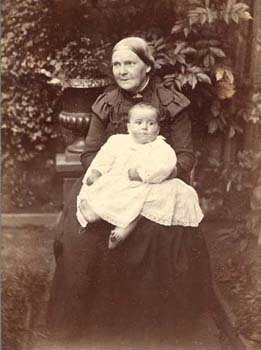 With her long dark dress and tied back hair, this elderly matron's appearance is typical of a late Victorian matriarch.